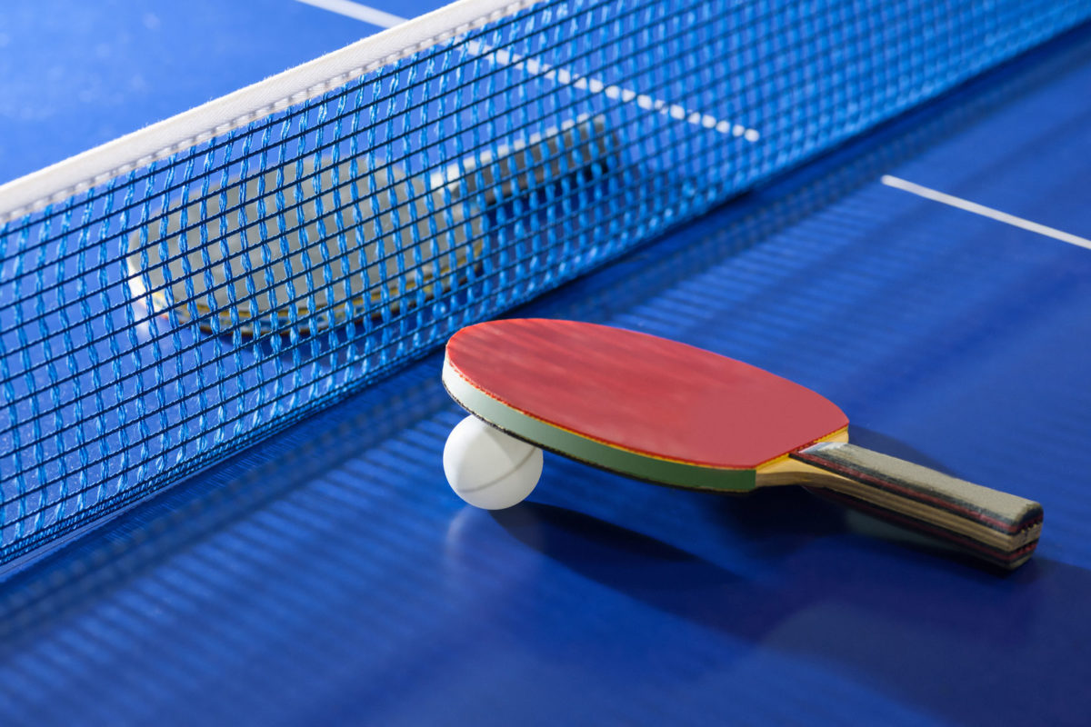 23887612 - table tennis rackets. top view of table tennis racket lying on the tennis table on the both sides of net